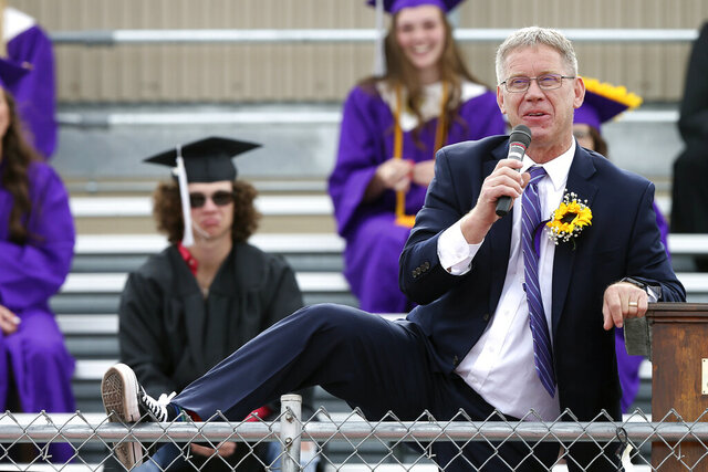 In this Sunday, May 17, 2020 photo, Laramie County School District No. 2 superintendent Jon Abrams shows off his Converse Chuck Taylor shoes while giving a speech during the 2020 Pine Bluffs Jr./Sr. High School graduation in Pine Bluffs, Wyo. Twenty-eight seniors sat in the bleachers, while families gathered on the football field to watch the ceremony. (Michael Cummo/The Wyoming Tribune Eagle via AP)