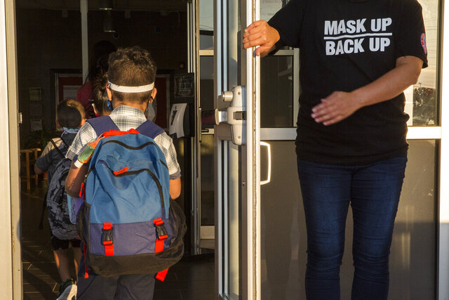 A staff member holds the door open for kids on the first day of school at Goodwin Frazier Elementary School in New Braunfels, Texas on Tuesday, Aug. 25, 2020. The number of Americans newly diagnosed with the coronavirus is falling — a development experts credit at least partly to increased wearing of masks — even as the outbreak continues to claim nearly 1,000 lives in the U.S. each day. (Mikala Compton/Herald-Zeitung via AP)