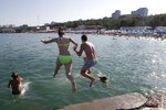 A couple jump into a water as they enjoy the beach in the Black Sea in Odessa, Ukraine, Saturday, July 4, 2020. Tens of thousands of vacation-goers in Russia and Ukraine have descended on Black Sea beaches, paying little attention to safety measures despite levels of contagion still remaining high in both countries. (AP Photo/Sergei Poliakov)
