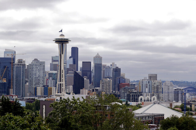 A flag with the new logo for the newly-named Seattle NHL hockey team, the Seattle Kraken, flies atop the iconic Space Needle and in view of the team's arena, lower right, Thursday, July 23, 2020, in Seattle. The hockey expansion franchise unveiled its nickname Thursday, ending 19 months of speculation about whether the team might lean traditional or go eccentric with the name for the league's 32nd team. Seattle's colors are a deep dark blue with a lighter shade of blue as a complement. (AP Photo/Elaine Thompson)