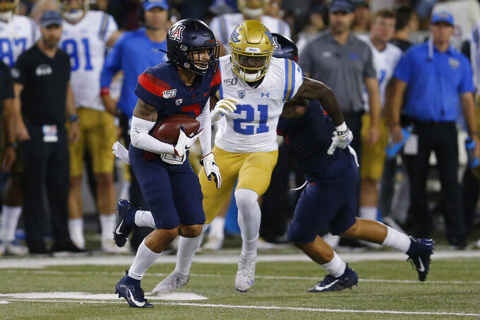 CORRECTS MONTH TO SEPTEMBER INSTEAD OF OCTOBER - Arizona cornerback Lorenzo Burns (2) runs with the ball after intercepting a pass against UCLA in the first half during an NCAA college football game, Saturday, Sept. 28, 2019, in Tucson, Ariz. (AP Photo/Rick Scuteri)