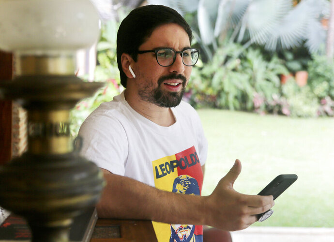 In this Saturday, May 11, 2019 photo, Venezuelan opposition leader Freddy Guevara, exiled at the Chilean ambassador's residence speaks by phone prior a interview with the Associated Press, in Caracas, Venezuela. Guevara, in his first televised interview since taking refuge in the lush diplomatic compound 18 months ago, said as foreign embassies in Caracas fill up with dissidents the world will be forced to take notice of how Nicolas Maduro's clinging to power is not only inflicting more damage on what's left of the rule of law in Venezuela but spilling over its borders as well. (AP Photo/Fernando Llano)