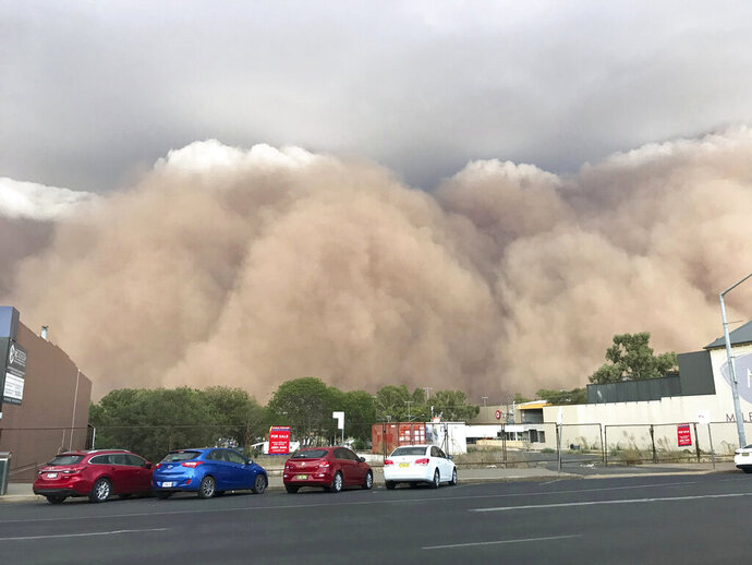 In this Sunday, Jan. 19, 2020, photo, a dust cloud billows over a street in Dubbo, Australia, 400 kms (248 miles) west of Sydney. Wind gusts of 107 kilometers an hour (66 mph) were recorded in Dubbo as the dust storm descended over the town. (Ian Harris via AP)