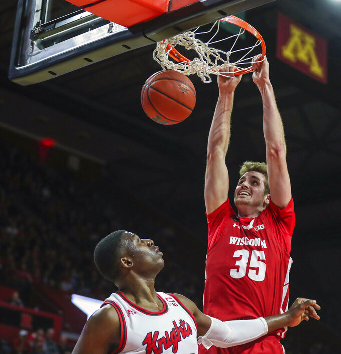 Wisconsin forward Nate Reuvers (35) dunks on Rutgers forward Shaq Carter (13) during the first half of an NCAA college basketball game in Piscataway, N.J., Wednesday, Dec. 11, 2019. (Andrew Mills/NJ Advance Media via AP)