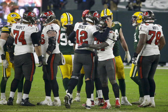 Tampa Bay Buccaneers quarterback Tom Brady (12) is congratulated by his teammate after winning the NFC championship NFL football game against the Green Bay Packers in Green Bay, Wis., Sunday, Jan. 24, 2021. The Buccaneers defeated the Packers 31-26 to advance to the Super Bowl. (AP Photo/Mike Roemer)