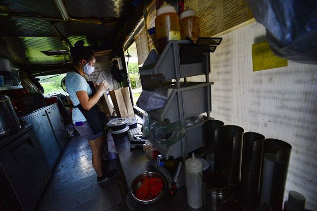 Emily Keopraseuth in a face mask packs meal orders for pick-up at the Taste of Thai food truck located at Mobil Station during the coronavirus pandemic, in Brattleboro, Vt., on Wednesday, Aug. 12, 2020. (Kristopher Radder/The Brattleboro Reformer via AP)