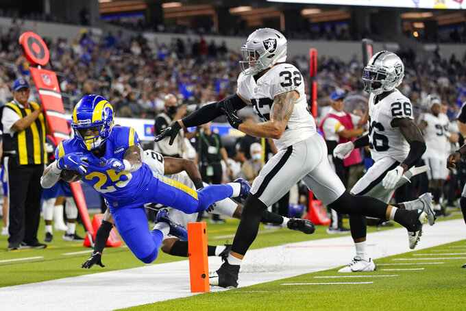 Los Angeles Rams running back Xavier Jones, left, is pushed out of bounds near the end zone by Las Vegas Raiders defensive back Dallin Leavitt (32) during the first half of a preseason NFL football game Saturday, Aug. 21, 2021, in Inglewood, Calif. (AP Photo/Ashley Landis)