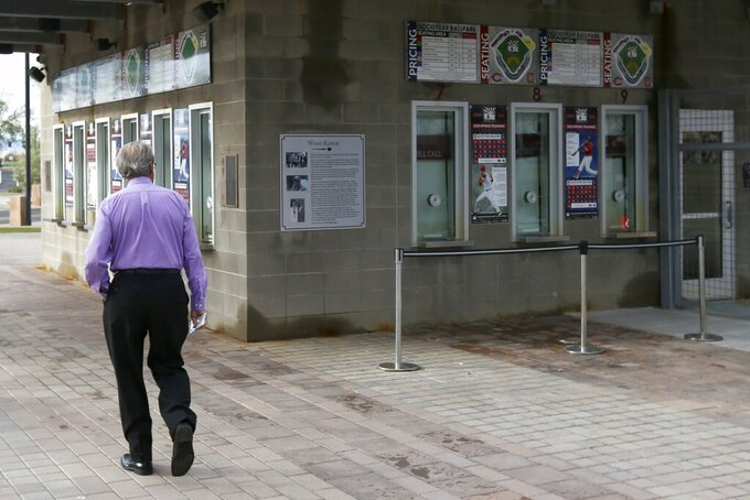 A ticket holder walks around the outside of Goodyear Ballpark, spring training home of the Cleveland Indians and Cincinnati Reds baseball teams, looking to get a refund on his canceled game tickets Thursday, March 12, 2020, in Goodyear, Ariz. Major League Baseball has suspended the rest of its spring training game schedule because if the coronavirus outbreak. MLB is also delaying the start of its regular season by at least two weeks. (AP Photo/Ross D. Franklin)