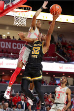 Houston guard Caleb Mills, left, knocks down a shot-attempt by Wichita State guard Grant Sherfield (52) during the first half of an NCAA college basketball game Sunday, Feb. 9, 2020, in Houston. (AP Photo/Michael Wyke)