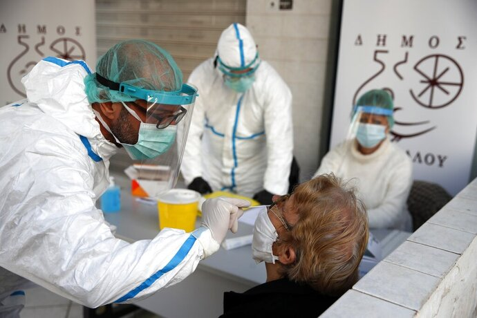 Medical staff conducts a rapid COVID test on an elderly woman in Athens, Monday, Nov. 23, 2020. Greece has seen a major resurgence of the virus after the summer, leading to dozens of deaths each day and thousands of new infections. (AP Photo/Thanassis Stavrakis)