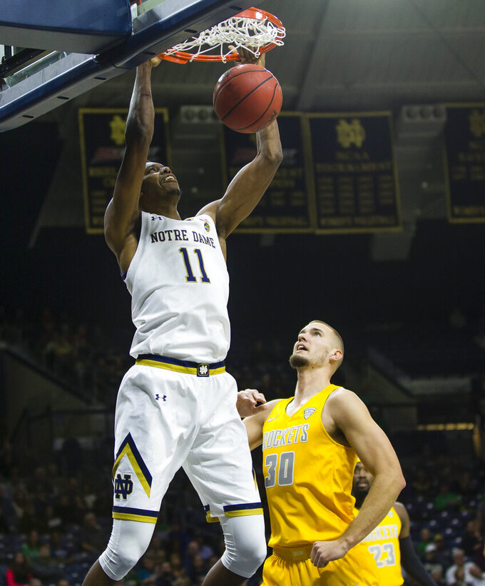 Notre Dame's Juwan Durham (11) dunks over Toledo's Luke Knapke (30) during an NCAA college basketball game Thursday, Nov. 21, 2019, in South Bend, Ind. (Michael Caterina/South Bend Tribune via AP)