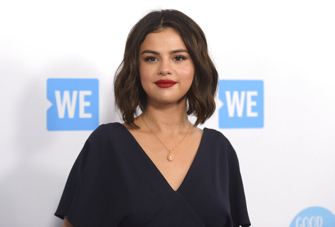 "FILE - Selena Gomez arrives at WE Day California on April 19, 2018, in Inglewood, Calif. Gomez is taking the heat in the kitchen. The singer-actress slices and dices in ""Selena + Chef,"" debuting Aug. 13 on the new HBO Max streaming service. The 10-episode series was shot in the kitchen of Gomez's new Los Angeles-area house. Her grandparents and two friends, who have been quarantining with her, serve as taste testers. (Photo by Richard Shotwell/Invision/AP, File)"