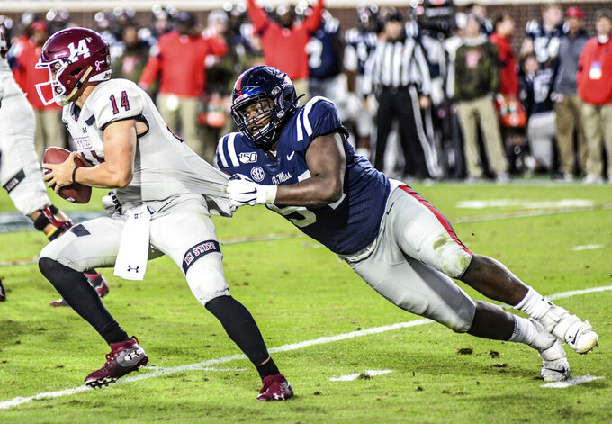 New Mexico State quarterback Josh Adkins (14) is sacked by Mississippi defensive end Quentin Bivens (94) during an NCAA college football game in Oxford, Miss., Saturday, Nov. 9, 2019. (Bruce Newman/The Oxford Eagle via AP)