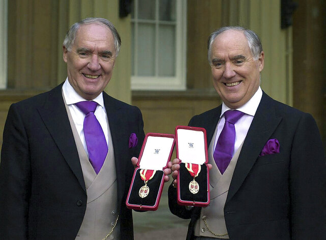 FILE - In this file photo dated Oct. 31, 2000, showing multi-millionaires David Barclay, left, standing with his twin brother Frederick Barclay, after receiving their knighthoods from the Queen at Buckingham Palace in London.  Joint-owner of the The Daily Telegraph national newspaper, David Barclay has died after a short illness aged 86, the newspaper has reported Wednesday Jan. 13, 2021. (Michael Stephens/PA FILE via AP)