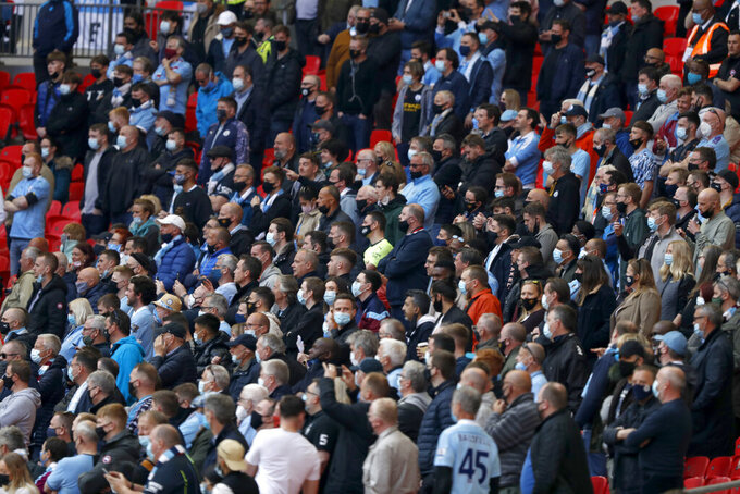 Manchester City fans stand up during the English League Cup final soccer match between Manchester City and Tottenham Hotspur at Wembley stadium in London, Sunday, April 25, 2021. Some eight thousand spectators were allowed in the stadium. (AP Photo/Alastair Grant)