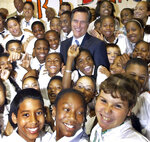 FILE - In this Sept. 18, 2003, file photo, Massachusetts Gov. Mitt Romney laughs as he poses with sixth, seventh and eighth graders from the Boston Renaissance Charter School in Boston. Romney's run for U.S. Senate in Utah is his latest bid for public office since he first jumped into politics more than 20 years ago. (AP Photo/Elise Amendola, File)