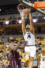 Missouri's Reed Nikko, right, dunks the ball over Texas A&M's Josh Nebo, left, during the second half of an NCAA college basketball game Tuesday, Jan. 21, 2020, in Columbia, Mo. Texas A&M won the game 66-64. (AP Photo/L.G. Patterson)