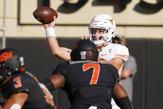 Texas quarterback Sam Ehlinger throws under pressure from Oklahoma State linebacker Amen Ogbongbemiga (7) during the first half of an NCAA college football game in Stillwater, Okla., Saturday, Oct. 31, 2020. (AP Photo/Sue Ogrocki)