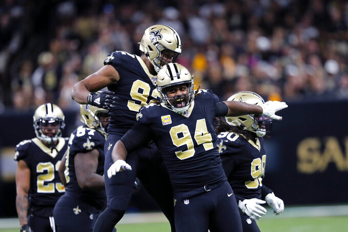 New Orleans Saints defensive end Cameron Jordan (94) and defensive end Marcus Davenport (92) celebrate a sack in the second half of an NFL football game against the Tampa Bay Buccaneers in New Orleans, Sunday, Oct. 6, 2019. The Saints won 31-24.(AP Photo/Bill Feig)