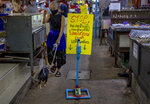 A woman walks her dog past a hand sanitizer positioned in an amulet market in Bangkok, Thailand, Tuesday, June 2, 2020. Amulet markets were allowed to reopen on Monday, June 1, 2020 as the Thai government continues to ease restrictions related to running business in the capital Bangkok that were imposed weeks ago to combat the spread of COVID-19. Believers in amulets say they can bring good fortune, true love or just about anything else. Sign reads as