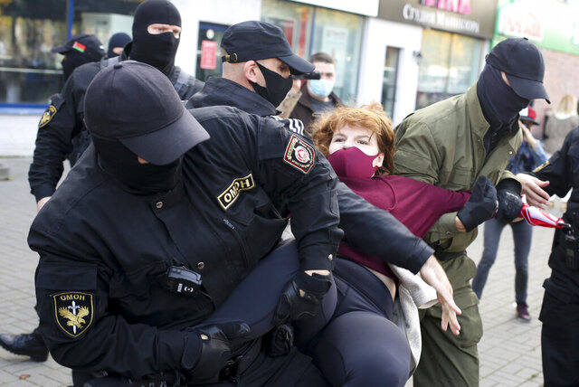 Police officers detain a woman during an opposition rally to protest the official presidential election results in Minsk, Belarus, Saturday, Sept. 19, 2020. Daily protests calling for the authoritarian president's resignation are now in their second month and opposition determination appears strong despite the detention of protest leaders. (AP Photo/TUT.by)