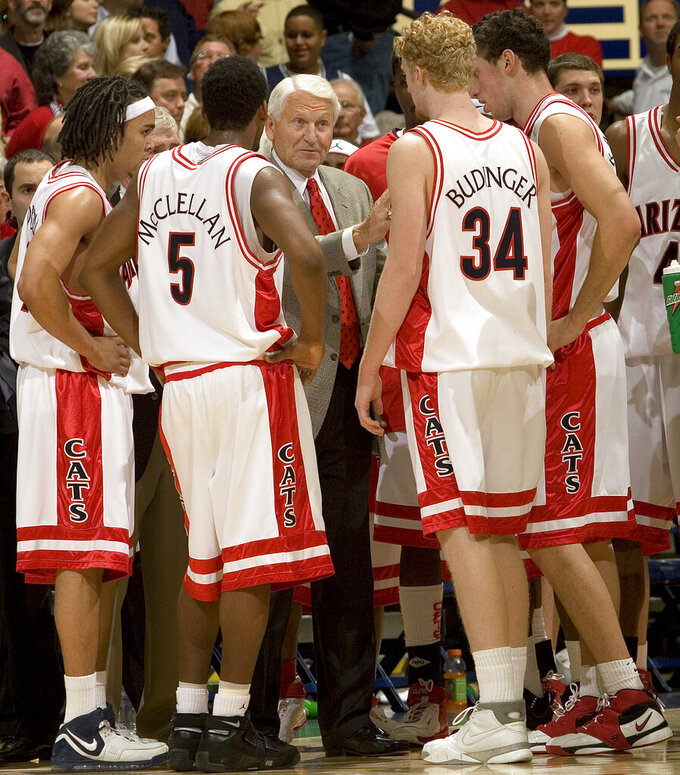FILE - In this Dec. 20, 2006, file photo, Arizona head coach Lute Olson, center, talks to his players, from left to right, Daniel Dillon, Jawann McClellan (5), Chase Budinger (34) and Ivan Radenovic during the second half of a college basketball game against Memphis in Tucson, Ariz. Olson, the Hall of Fame coach who turned Arizona into a college basketball powerhouse, has died at the age of 85. Olson's family said he died Thursday, Aug. 27, 2020. The family did not provide the cause of death. (AP Photo/John Miller, File)
