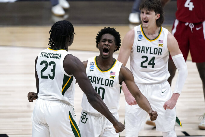 Baylor guard Adam Flagler (10), Jonathan Tchamwa Tchatchoua (23) and Matthew Mayer (24) celebrate a play against Arkansas during the second half of an Elite 8 game in the NCAA men's college basketball tournament at Lucas Oil Stadium, Monday, March 29, 2021, in Indianapolis. (AP Photo/Michael Conroy)