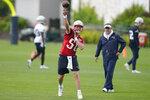 New England Patriots quarterback Mac Jones (50) passes the ball as offensive coordinator Josh McDaniels, center right, looks on during an NFL football practice, Monday, June 14, 2021, in Foxborough, Mass. (AP Photo/Steven Senne)