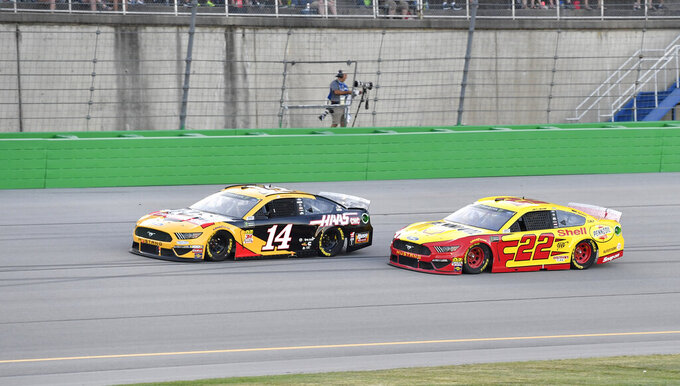 Clint Bowyer (14) attempts to hold off the challenge of Joey Logano (22) during the NASCAR Cup Series auto race at Kentucky Speedway in Sparta, Ky., Saturday, July 13, 2019. (AP Photo/Timothy D. Easley)
