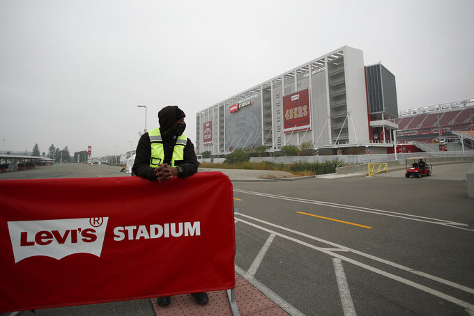 FILE - In this Sept. 13, 2020, file photo, a worker stands outside of Levi's Stadium before an NFL football game between the San Francisco 49ers and the Arizona Cardinals in Santa Clara, Calif. California officials ramped up more mass coronavirus vaccination sites Friday, Feb. 5, 2021, amid a critical supply shortage, with one San Francisco Bay Area county announcing a mega-site capable of 15,000 shots a day even as another said it stopped first doses to ration enough for those needing their second inoculation. Santa Clara County and the 49ers said they will open California's largest vaccination site at Levi's Stadium early next week, eventually capable of injecting up to 15,000 people each day as supplies allow. (AP Photo/Josie Lepe, File)