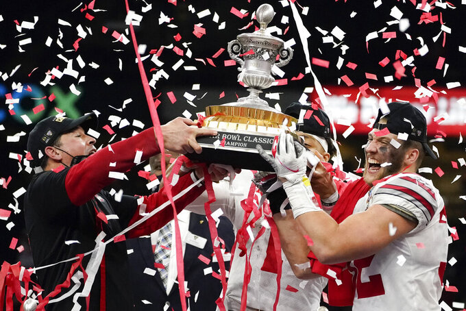 Ohio State head coach Ryan Day, from left, quarterback Justin Fields and linebacker Tuf Borland hold up the trophy after their teams win against Clemson in the Sugar Bowl NCAA college football game Friday, Jan. 1, 2021, in New Orleans. Ohio State won 49-28. (AP Photo/John Bazemore)