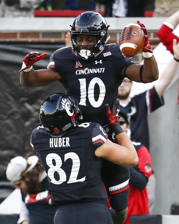 Cincinnati running back Charles McClelland (10) celebrates his touchdown with tight end Wilson Huber (82) in the second half of an NCAA college football game against Navy, Saturday, Nov. 3, 2018, in Cincinnati. (AP Photo/John Minchillo)