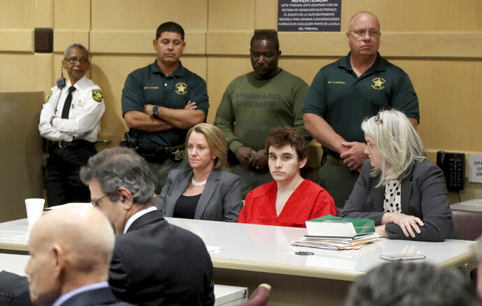 FILE - In this Wednesday, May 1, 2019 file photo, Parkland school shooting suspect Nikolas Cruz sits in court at the Broward Courthouse in Fort Lauderdale, Fla., for a motion by the Public Defender's Office to withdraw from the case due to Cruz receiving an inheritance that can be used to pay for a private attorney. A public defender must continue representing the former student charged in last year's Florida high school massacre,  Judge Elizabeth Scherer ruled Friday, May 3, 2019 saying it's unlikely that Nikolas Cruz will actually receive a large inheritance left by his late mother. (Mike Stocker/South Florida Sun-Sentinel via AP, Pool, File)