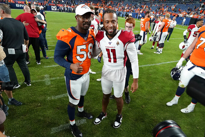 FILE - In this Aug. 29, 2019, file photo, Denver Broncos outside linebacker Von Miller (58) greets Arizona Cardinals wide receiver Larry Fitzgerald (11) after an NFL preseason football game in Denver. The NFL will cut its preseason in half and push back the start of exhibition play so teams have more time to train following an all virtual offseason made necessary by the coronavirus pandemic, a person with knowledge of the decision told The Associated Press. The person spoke on condition of anonymity because the league hasn't announced that the preseason will be cut from four games to two. (AP Photo/Jack Dempsey, File)