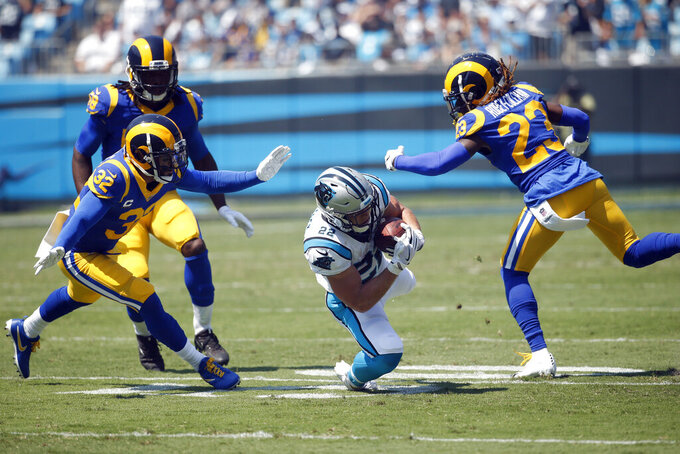 Carolina Panthers running back Christian McCaffrey (22) is tripped up while Los Angeles Rams free safety Eric Weddle (32) and defensive back Nickell Robey-Coleman (23) move in to tackle during the first half an NFL football game in Charlotte, N.C., Sunday, Sept. 8, 2019. (AP Photo/Brian Blanco)