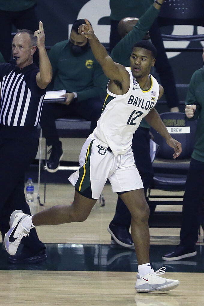 FILE - Baylor guard Jared Butler (12) reacts after making a three-point shot against Oklahoma State in the second half of an NCAA college basketball game in Waco, Texas, in this Thursday, March 4, 2021, file photo. Baylor guard Jared Butler is The Associated Press Big 12 men's basketball player of the year and a member of the All-Big 12 first team, announced Tuesday, March 9, 2021.(AP Photo/Jerry Larson)