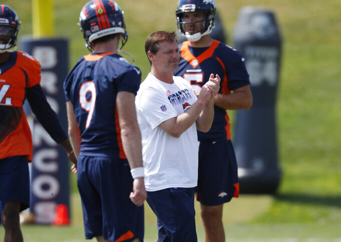 Denver Broncos offensive coordinator Rich Scangarello, center, directs quarterbacks Kevin Hogan (9) and Joe Flacco during an NFL football practice Tuesday, Aug. 27, 2019, at the team's headquarters in Englewood, Colo. (AP Photo/David Zalubowski)