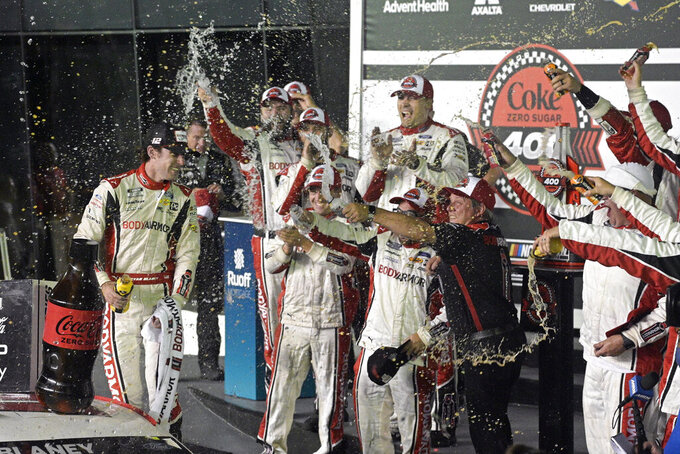 Ryan Blaney, left, celebrates in Victory Lane with crew members after winning the NASCAR Cup Series auto race at Daytona International Speedway, Saturday, Aug. 28, 2021, in Daytona Beach, Fla. (AP Photo/Phelan M. Ebenhack)