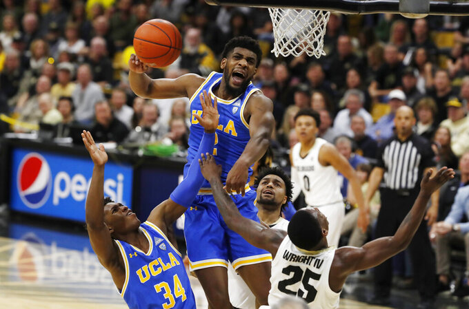 UCLA forward Cody Riley, center, blocks a shot by Colorado guard McKinley Wright IV, right, as UCLA guard David Singleton pulls in the loose ball in the second half of an NCAA college basketball game Saturday, Feb. 22, 2020, in Boulder, Colo.  (AP Photo/David Zalubowski)sc