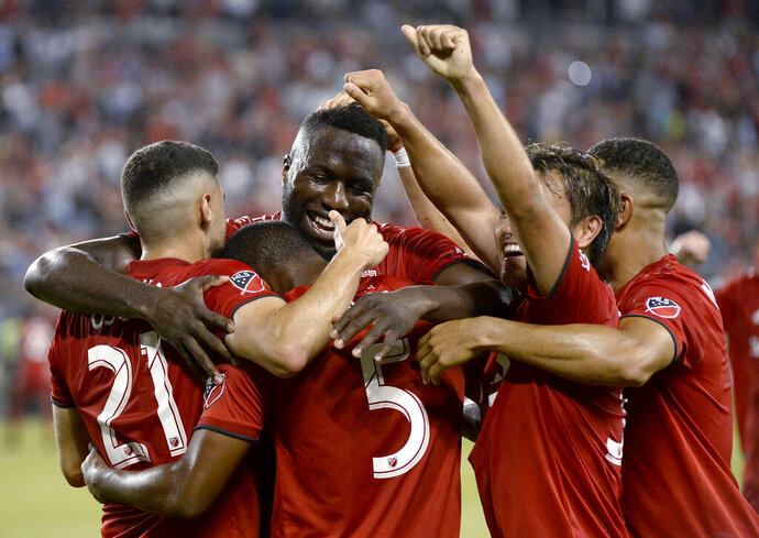 Toronto FC defender Ashtone Morgan (5) gets mobbed by teammates after scoring against the New York Red Bulls during the second half of an MLS soccer match Wednesday, July 17, 2019, in Toronto. (Nathan Denette/The Canadian Press via AP)