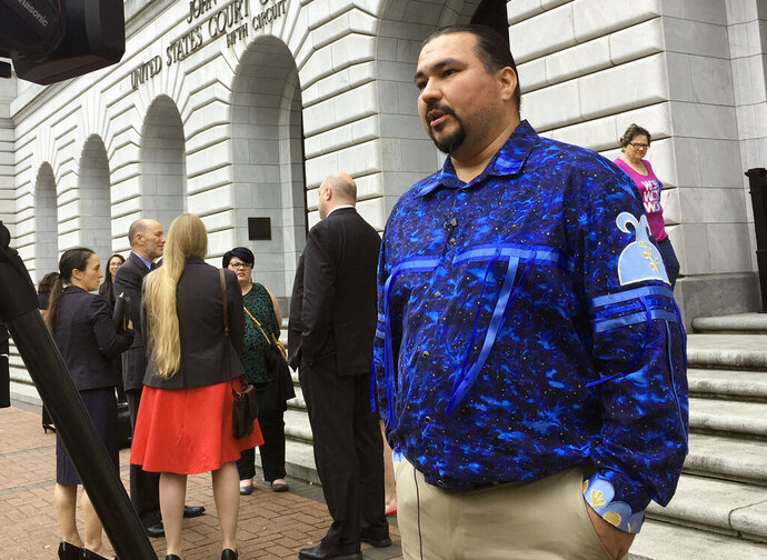 FILE - In this March 13, 2019, file photo, Tehassi Hill, tribal chairman of the Oneida Nation, stands outside a federal appeals court in New Orleans, following arguments on the constitutionality of a 1978 law giving Native American families preference in adoption of Native American children. A federal appeals court says it will take a second look at an emotionally fraught lawsuit governing the adoption of Native American children. In August, a three-judge panel of the 5th U.S. Circuit Court of Appeals upheld the Indian Child Welfare Act of 1978. On Thursday, Nov. 7 the New Orleans-based court said a majority of its active judges have voted to re-hear the case. (AP Photo/Kevin McGill, File)