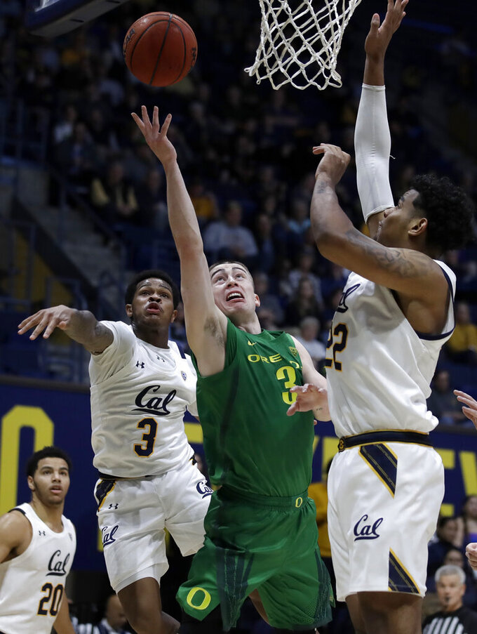 Oregon's Payton Pritchard, center, lays up a shot between California's Paris Austin, left, and Andre Kelly in the first half of an NCAA college basketball game Thursday, Jan. 30, 2020, in Berkeley, Calif. (AP Photo/Ben Margot)