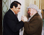 FILE - In this Oct. 1, 2001 file photo, Tunisian President Zine El Abidine Ben Ali, left, welcomes Palestinian leader Yasser Arafat prior to their talks in Tunis. Tunisia's autocratic ruler Zine El Abidine Ben Ali, toppled in 2011, died in exile in Saudi Arabia. (AP Photo/File)