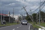 Vehicles pass by toppled electrical poles as Typhoon Kammuri slammed Legazpi city, Albay province, southeast of Manila, Philippines on Tuesday, Dec. 3, 2019. A powerful typhoon was blowing across the Philippines on Tuesday after slamming ashore overnight in an eastern province, damaging houses and an airport and knocking out power after tens of thousands of people fled to safer ground. (AP Photo)