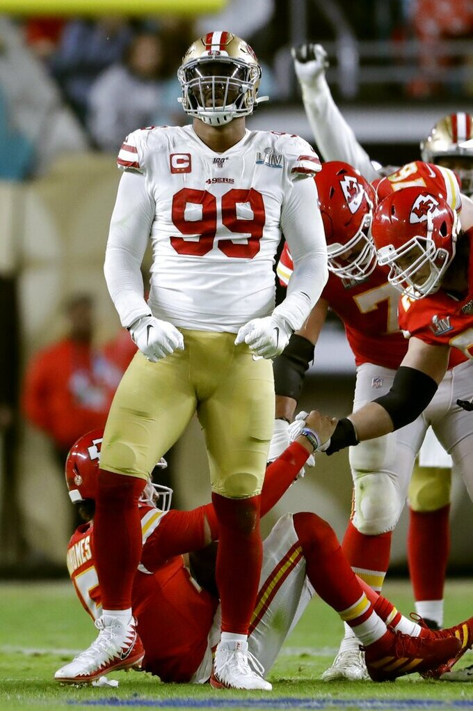 San Francisco 49ers' DeForest Buckner, front, celebrates his sack of Kansas City Chiefs' quarterback Patrick Mahomes, on the turf rear, during the second half of the NFL Super Bowl 54 football game Sunday, Feb. 2, 2020, in Miami Gardens, Fla. (AP Photo/John Bazemore)