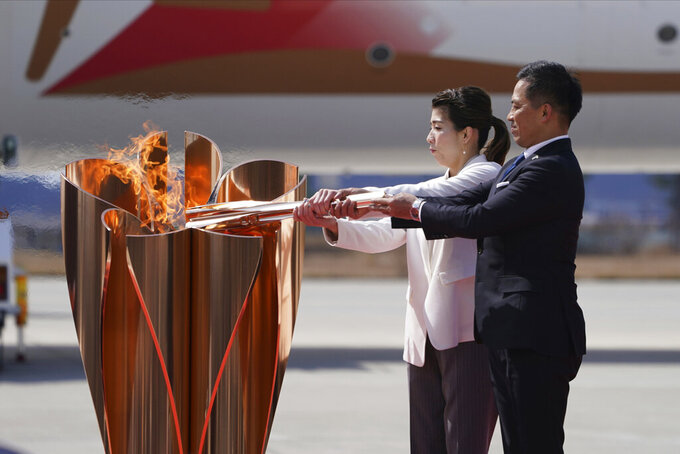 FILE - In this March 20, 2020, file photo, three-time Olympic gold medalists Tadahiro Nomura, right, and Saori Yoshida light the torch during Olympic Flame Arrival Ceremony at Japan Air Self-Defense Force Matsushima Base in Higashimatsushima in Miyagi Prefecture, north of Tokyo. The torch relay for the postponed Tokyo Olympics is to start in just over three months, and it faces the same questions as the Olympics about being held safely during the coronavirus pandemic. (AP Photo/Eugene Hoshiko, File)