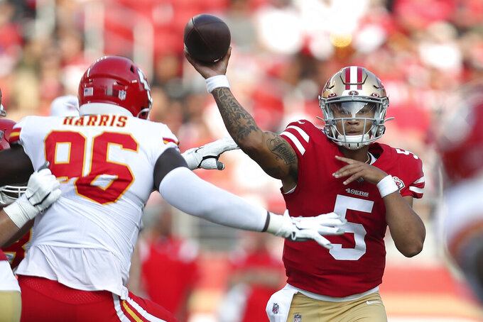 FILE - In this Aug. 14, 2021, file photo, San Francisco 49ers quarterback Trey Lance (5) throws a pass as Kansas City Chiefs defensive end Demone Harris (96) pressures during the first half of an NFL preseason football game in Santa Clara, Calif. Switching personnel mid-drive is commonplace in the NFL with running backs shuttling in and out and teams switching from three-receiver sets to two-receiver formations all the time. The 49ers could do it at quarterback this season with Jimmy Garoppolo and rookie Trey Lance sharing time.  (AP Photo/Jed Jacobsohn, File)