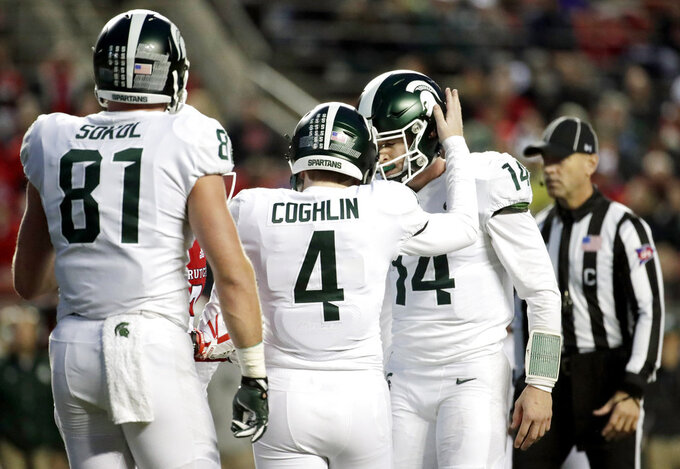 Michigan State placekicker Matt Coghlin (4) is congratulated by Brian Lewerke, right, after making a field goal against Rutgers during the first half of an NCAA college football game, Saturday, Nov. 25, 2017, in Piscataway, N.J. (AP Photo/Julio Cortez)