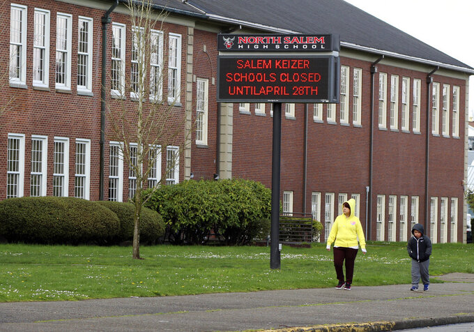 A woman and child walk past North Salem High School on Tuesday, March 31, 2020, which like all schools in Oregon, is closed until April 28, 2020, because of the coronavirus. Facing an expected closure through the end of the academic year, schools across Oregon have been told to begin distance learning on April 13, 2020. (AP Photo/Andrew Selsky)