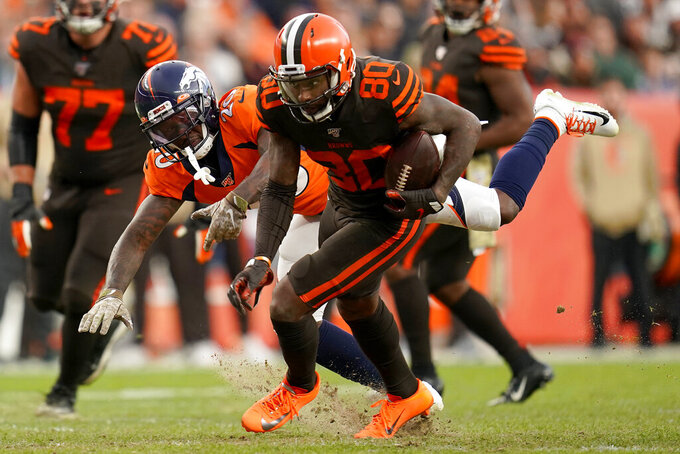 Cleveland Browns wide receiver Jarvis Landry (80) eludes Denver Broncos defensive back Duke Dawson (20) during the second half of NFL football game, Sunday, Nov. 3, 2019, in Denver. (AP Photo/Jack Dempsey)